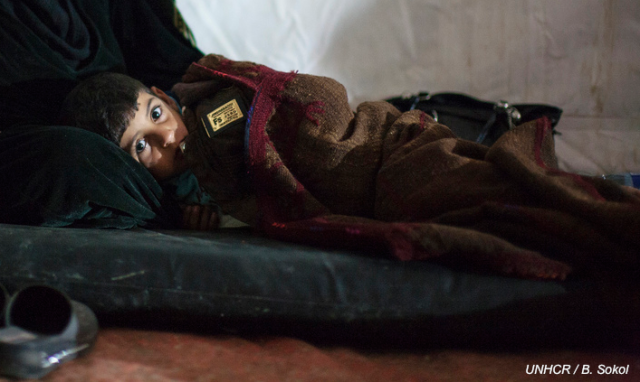 A young Syrian boy stays warm in Jordan's Za'atri refugee camp
