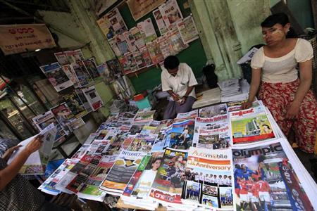 Vendors sit at a roadside newspaper and journals shop in Yangon April 1, 2013.