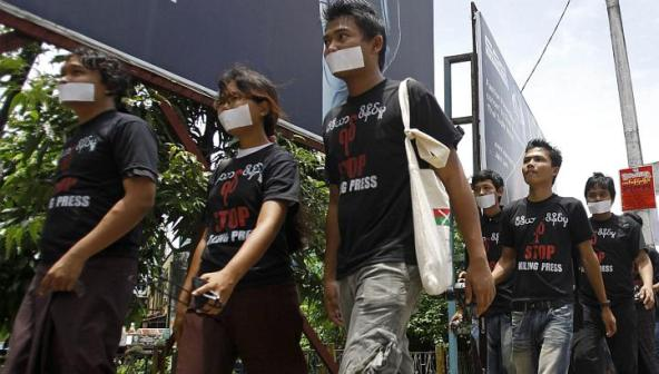 "This AFP photo shows Burma's journalists walked as they wear shirts displaying their campaign slogan ""Stop Killing Press"" and tape across their mouths during a rally in Yangon on Aug 4, 2012"